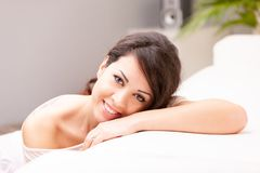 Beautiful coy woman smiling on her sofa. Beautiful coy expression of a woman lying on her arm on a sofa in her living room stock photos