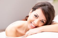 Beautiful coy woman smiling on her sofa. Beautiful coy expression of a woman lying on her arm on a sofa in her living room royalty free stock photos
