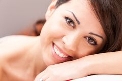 Beautiful coy woman smiling on her sofa. Beautiful coy expression of a woman lying on her arm on a sofa in her living room stock images