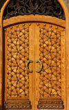 Beautiful crafted wooden arabesque door. Libya Bengazhi beautiful crafted wooden arabesque door decorated with brass handles and islamic stars Royalty Free Stock Images