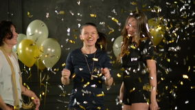 Beautiful Crazy Girls are Dancing among Golden and Silver Confetti that Falling Down. Three Pretty Women Having Fun stock footage