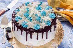 Beautiful cream cake decorated with chocolate leaks, cream and sugar snowflakes from mastic Stock Photo
