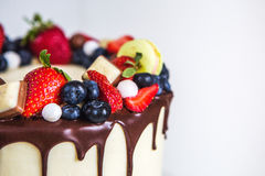 Beautiful cream colored cake decorated with strawberries, blueberries, chocolate, macaroon, standing on white wooden table royalty free stock image