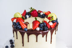 Beautiful cream colored cake decorated with strawberries, blueberries, chocolate, macaroon, standing on white wooden table stock photos