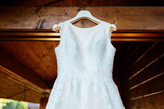 A beautiful cream wedding dress hanging on the wall. Near the wooden house Stock Photography