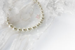 Beautiful creamy pearls necklace on lace background. Royalty Free Stock Image