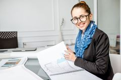 Architect working in the office. Beautiful creative architect or designer working with drawings in the office royalty free stock images