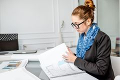 Architect working in the office. Beautiful creative architect or designer working with drawings in the office stock photo