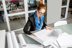 Architect working in the office. Beautiful creative architect woman working with drawings in the office royalty free stock photos