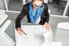 Architect working in the office. Beautiful creative architect woman working with drawings in the office royalty free stock images