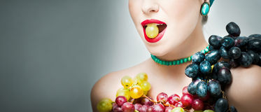 Beautiful creative makeup in fall concept, studio shot on gray background. Beauty fashion model girl with grapes arrangement Royalty Free Stock Photos