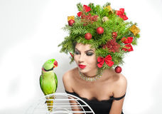 Beautiful creative Xmas makeup and hair style indoor shot. Beauty Fashion Model Girl with green parrot Stock Photo