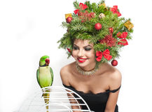 Beautiful creative Xmas makeup and hair style indoor shot. Beauty Fashion Model Girl with green parrot Stock Photography