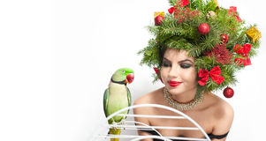Beautiful creative Xmas makeup and hair style indoor shot. Beauty Fashion Model Girl with green parrot Stock Photos