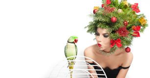 Beautiful creative Xmas makeup and hair style indoor shot. Beauty Fashion Model Girl with green parrot Stock Images