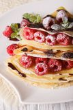 Beautiful crepes with raspberries and chocolate close-up. vertic. Beautiful crepes with fresh raspberries and chocolate close-up on a plate. vertical Stock Image