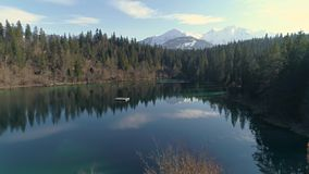 Beautiful Crestasee Lake Swiss Aerial 4k. Aerial footage of a beautiful lake in the forest with mountains in the background. Shot in Flims, Switzerland in 4k stock footage