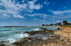 Beautiful Cretan rocky coastline with blue sea and surfers Stock Images