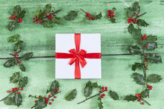 Beautiful Cristmas gifts i the middle of Holly on old green painted cracked wooden background Stock Photography