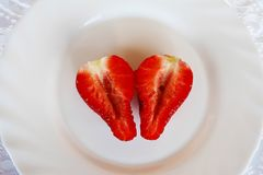 Beautiful cultivated deep red delicious strawberries, macro photography, decoration with fruit in white plate and white background. Beautiful cultivated deep red royalty free stock photos
