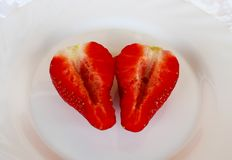 Beautiful cultivated deep red delicious strawberries, macro photography, decoration with fruit in white plate and white background. Beautiful cultivated deep red stock photography