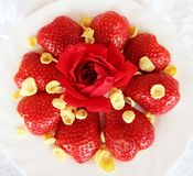 Beautiful cultivated deep red delicious strawberries, macro photography, decoration with fruit in white and rose flower. Beautiful cultivated deep red delicious stock photo