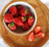 Beautiful cultivated deep red delicious strawberries, macro photography, decoration with fruit in white and wooden plate. With peaces, fresh stock photography
