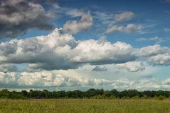 Beautiful cumulus clouds over the green valley Royalty Free Stock Photo