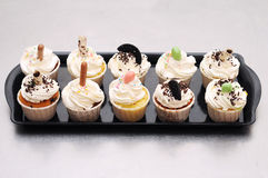 Beautiful cup cakes in black tray. On silver kitchen table Stock Image