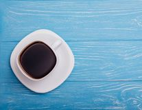 Beautiful cup of coffee on a blue background. A cup of white with a black coffee on a blue wooden table. Top view Stock Photos