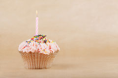 Beautiful Cupcake. With the burning candle on a beige background Stock Photos