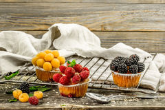 Beautiful cupcakes with berries on wooden background Stock Photos