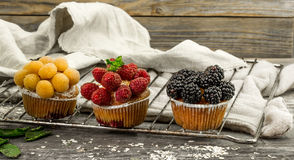 Beautiful cupcakes with berries on wooden background Royalty Free Stock Image