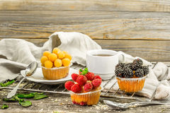 Beautiful cupcakes with berries on wooden background Stock Photo