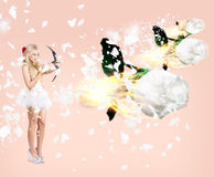 Beautiful cupid woman firing romance arrows. Marvellous young cupid woman shelling romantic fire arrows into the skies above when setting a heart ablaze Royalty Free Stock Images