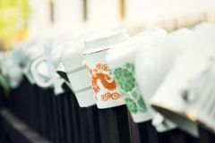 Beautiful cups laid upside down on wooden fence bars for wanderers refreshment, Asian dragon ornament, peace meditation wanderlust. Concept, Czech Republic royalty free stock photography