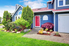 Beautiful curb appeal with blue exterior paint and red roof. Nice front landscape design Stock Images