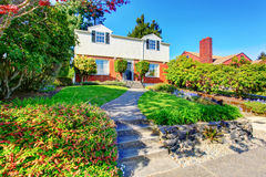 Beautiful Curb appeal of two level house with nice front garden and concrete walkway. . Stock Photography