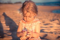 Beautiful curious child girl toddler playing on beach with hermit crab during summer vacation concept childhood lifestyle royalty free stock photography
