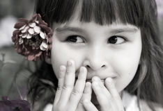 Beautiful curious girl with a flower in her hair Stock Photography