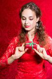 Beautiful curious girl with a small gift in a red dress Royalty Free Stock Photo