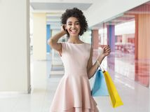 Beautiful curly african-american woman standing in shopping mall. Beautiful curly african-american woman standing with coloured shopping bags in shopping mall Stock Photos