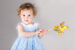 Beautiful curly baby girl in blue dress with wind toy Stock Images