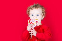 Beautiful curly baby girl eating a heart shaped candy on red bac. Kground Stock Photo