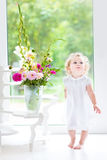 Beautiful curly baby girl with fresh flower bouquet Royalty Free Stock Images