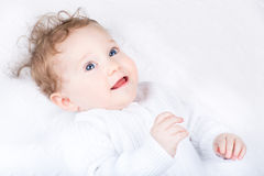 Beautiful curly baby on a white blanket Stock Images