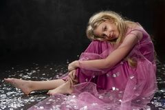 Beautiful curly blonde teenager child girl wearing a pink air dr. Ess made of veil smiles and sits on the floor in the middle of scattered spangles. Clean Stock Images