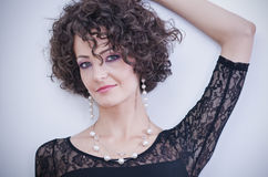 Beautiful curly brunette. Posing, head shot royalty free stock images