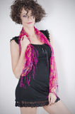 Beautiful curly brunette. With a red scarf, standing royalty free stock photography