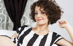 Beautiful curly brunette sitting on a couch Stock Photography